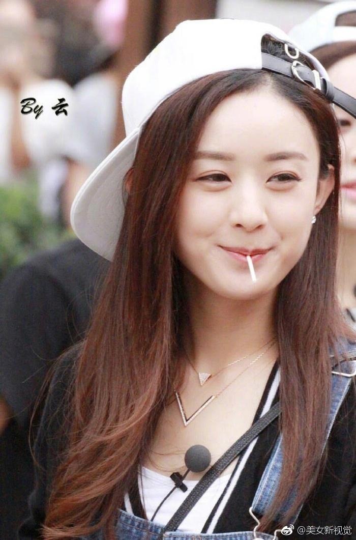赵丽颖机场被拍,头戴棒球帽手拿棒棒糖可爱又甜美.