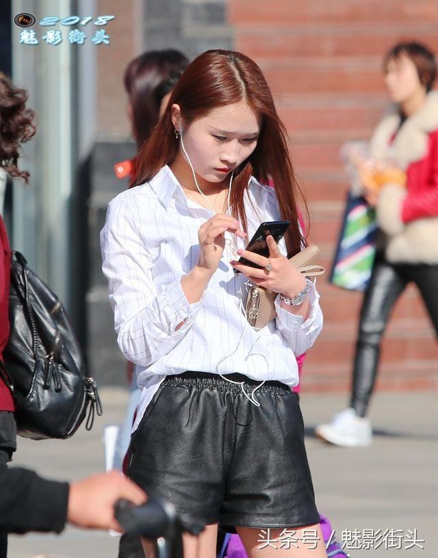 穿白美女、皮短裤、美女靴的衬衣站在街边玩着高筒的裤穿丁字透明图片